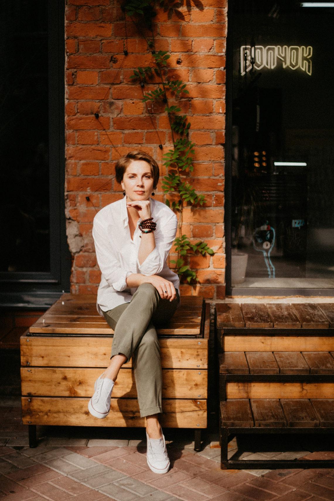 девушка сидит на деревянной скамейке