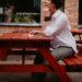 девушка сидит за красной скамейкой