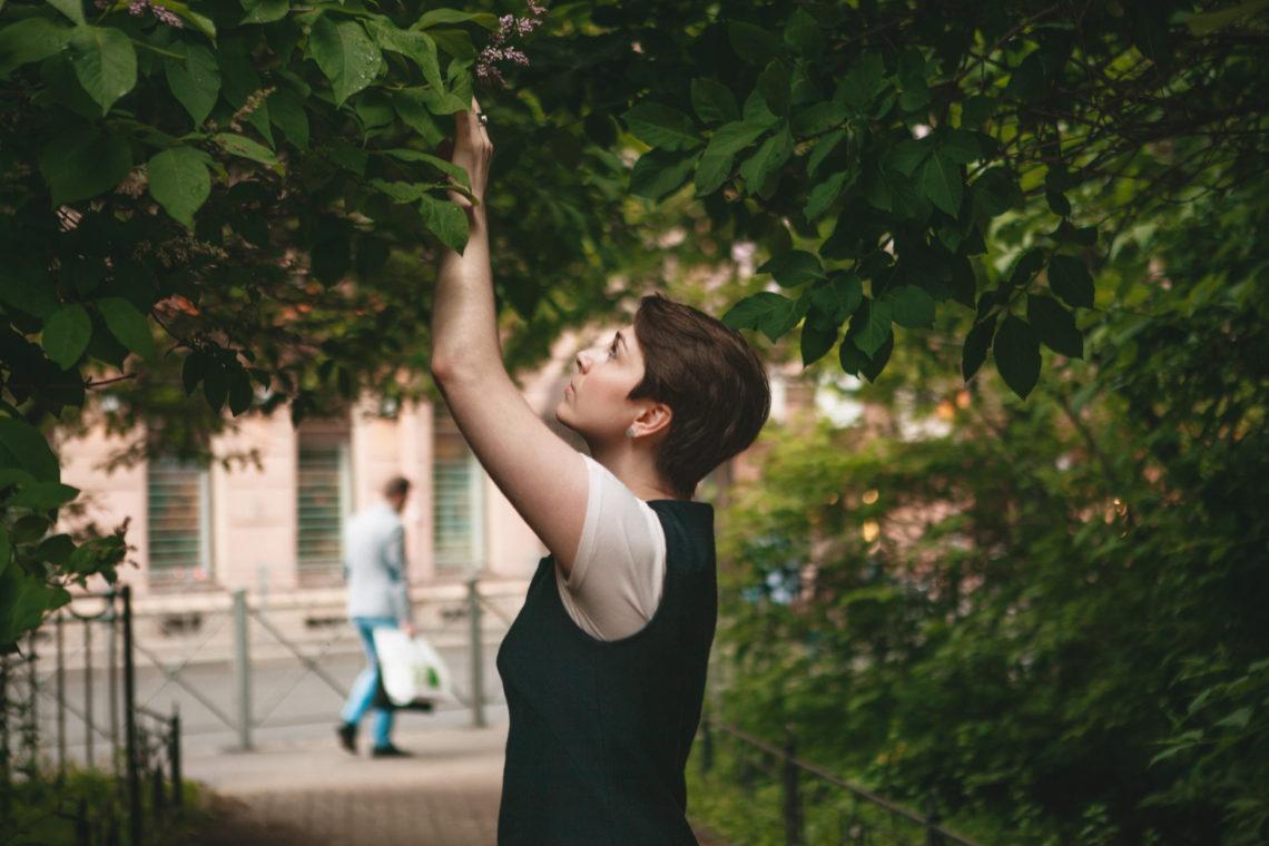 девушка ищет что-то в ветвях дерева