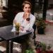 девушка сидит на веранде летнего кафе