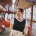девушка едет в красном трамвае