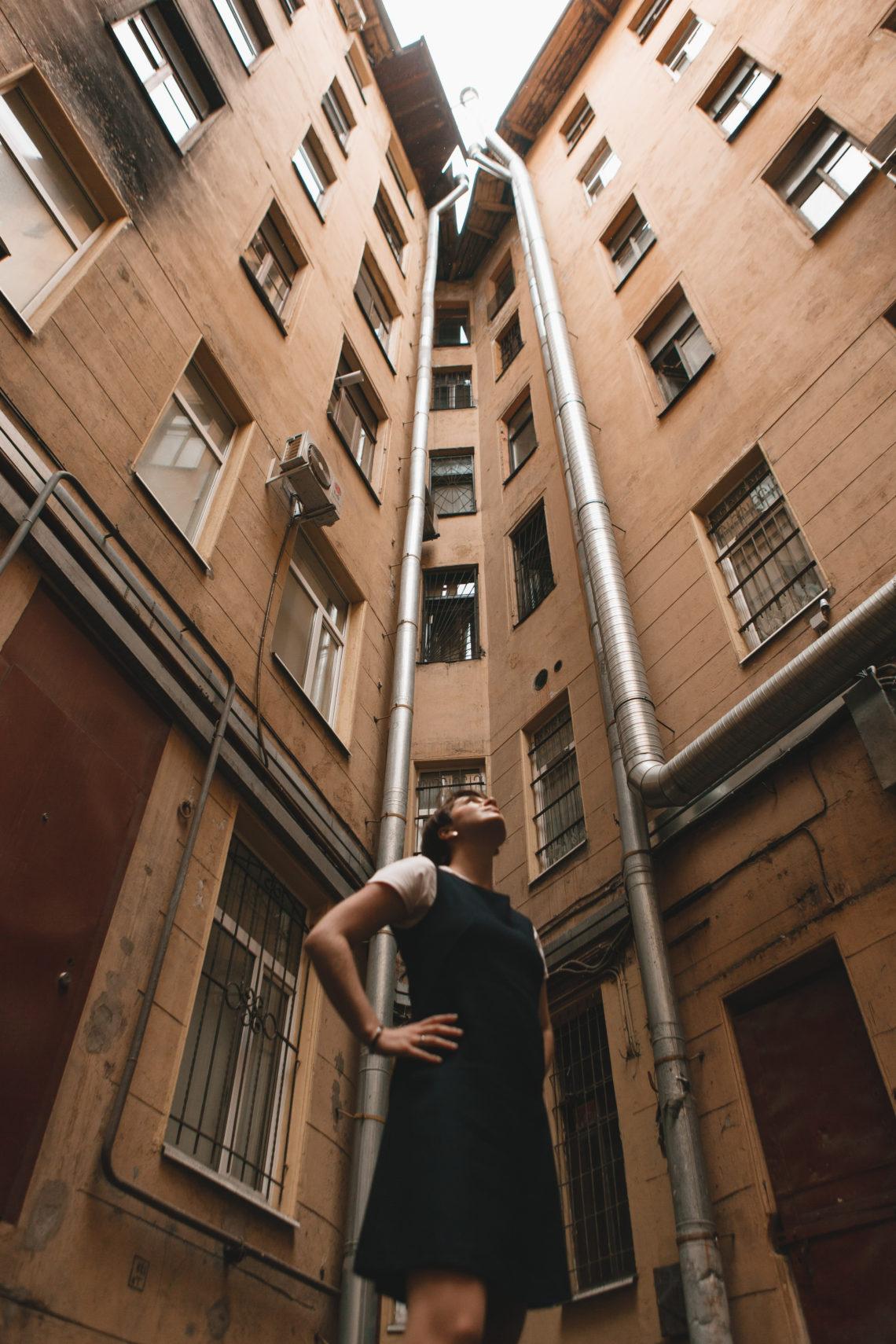 девущка стоит во дворе-колодце и смотрит наверх